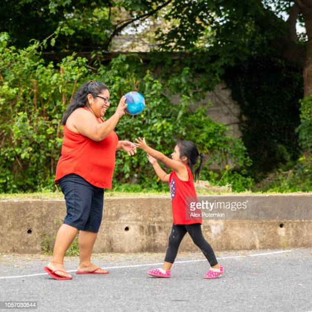 the body-positive, cheerful happy latino, mexican-american woman playing ball outdoor with her little daughter - alex potemkin or krakozawr latino fitness stock photos and pictures