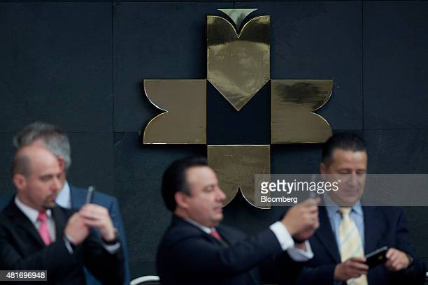 The Bolsa Mexicana de Valores logo is displayed as attendees take photos using mobile phones after Elementia SA executives rang the opening bell in...
