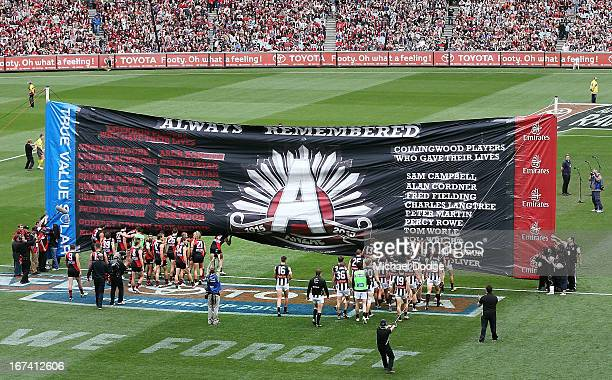 The Bombers and Magpies players walk towards the Anzac Day banner during the round five AFL match between the Essendon Bombers and the Collingwood...
