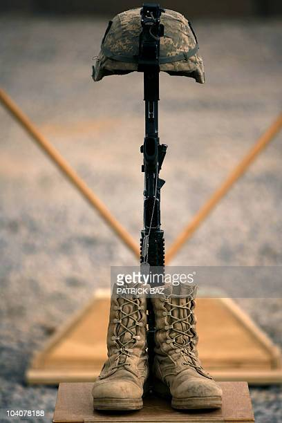 The boots gun helmet and dogtags of US army First Lieutenant Todd W Weaver are displayed during a memorial ceremony in his honor at Combat Outpost...