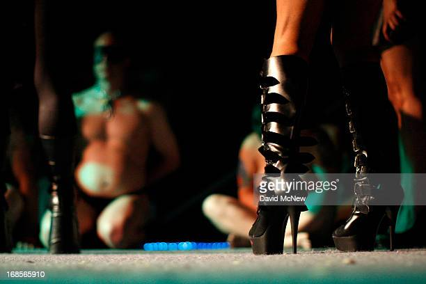 The boots of a dominatrix are seen as men and woman in a contest to be the best submissive kneel at a dungeon party during the domination convention...