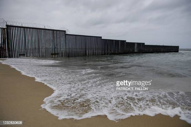 The border wall crosses the beach as it ends in the Pacific Ocean along the US-Mexico border between San Diego and Tijuana on May 10, 2021 at...