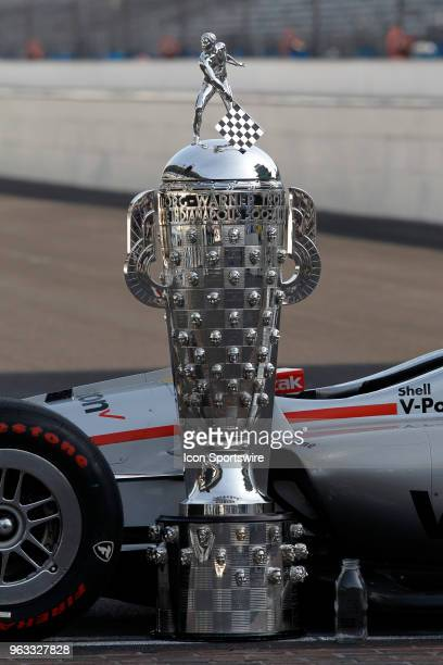 The BorgWarner Trophy along with a empty bottle of milk sit along side Indycar driver Will Power of Team Penske's car on the yard of bricks during...