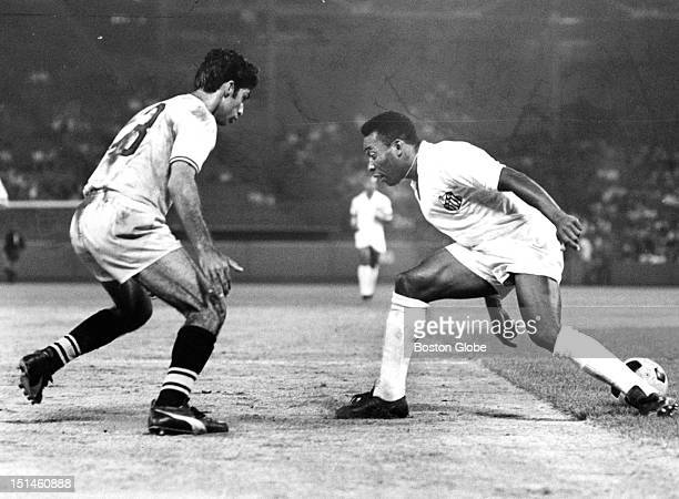 The Boston Beacons' Jorge Miguel , left, defends against Santos FC's Pele during a soccer game at Fenway Park, July 8, 1968.
