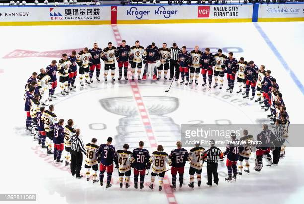 The Boston Bruins and the Columbus Blue Jackets gather at center ice prior to their exhibition game before the 2020 NHL Stanley Cup Playoffs at...