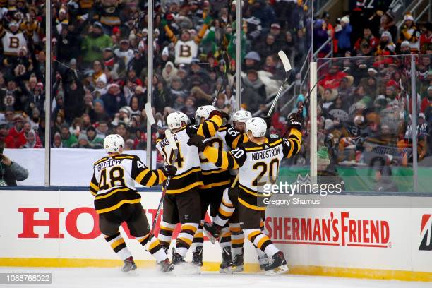 The Boston Bruins celebrate after Sean Kuraly scored a goal in the third period against the Chicago Blackhawks during the 2019 Bridgestone NHL Winter...
