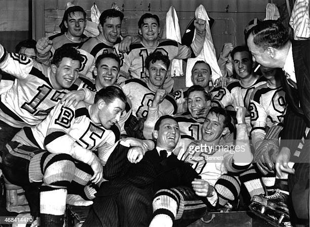 The Boston Bruins celebrate in the locker room with coach Cooney Weiland and general manager Art Ross after Game 4 of the 1941 Stanley Cup Finals...