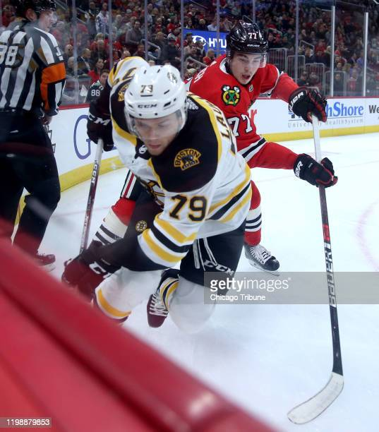 The Boston Bruins' Jeremy Lauzon tries to fend off the Chicago Blackhawks' Kirby Dach along the boards in the first period at the United Center in...