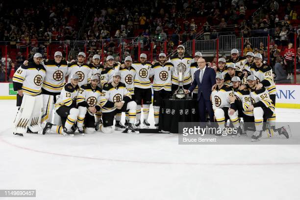 The Boston Bruins pose with the Deputy Commissioner Bill Daly and the Prince of Wales Trophy after defeating the Carolina Hurricanes in Game Four to...