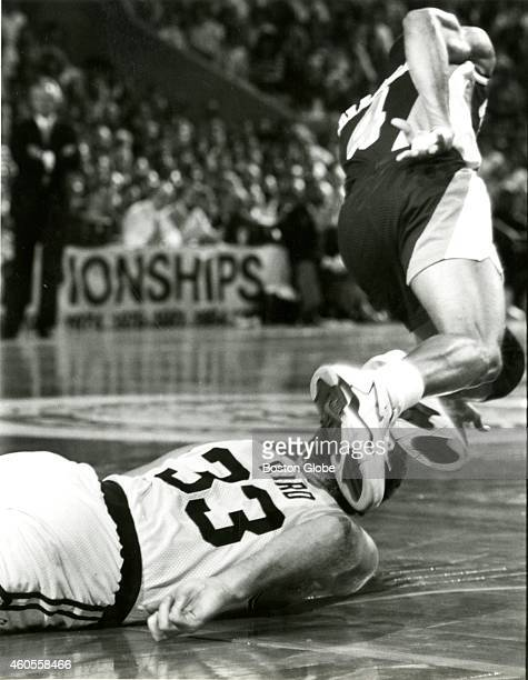 The Boston Celtics' Larry Bird hits his head on the parquet floor at the TD Garden as the Indiana Pacers' Micheal Williams trips over him