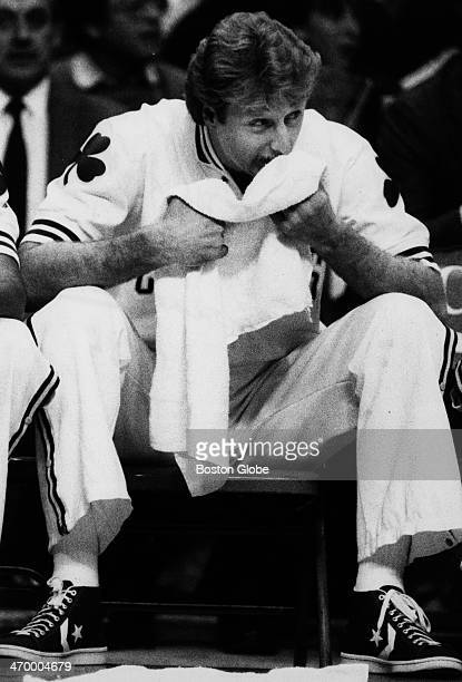 The Boston Celtics' Larry Bird uses a towel as he sists on the bench at Boston Garden Jan 16 1985