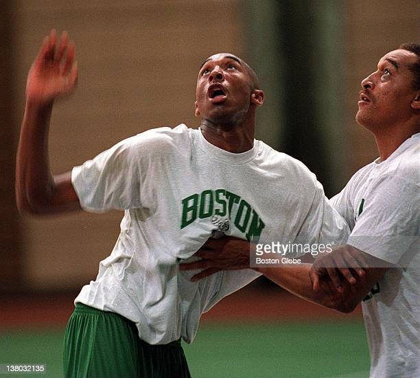 The Boston Celtics try out Kobe Bryant as coaches look on Kobe and Denis Johnson fight for the rebound