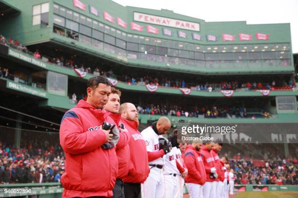 The Boston Red Sox bench stand during a moment of silence for the Boston Marathon bombings before the Boston Sox play the Baltimore Orioles at Fenway...