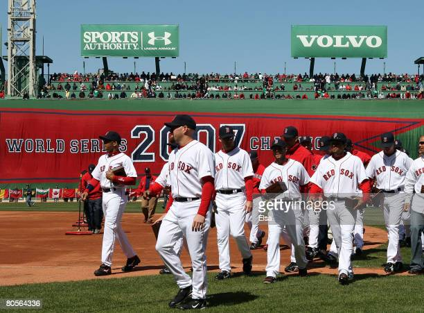 The Boston Red Sox head to the dugout after raising the 2007 World Series banner and carrying their championship rings before the game against the...