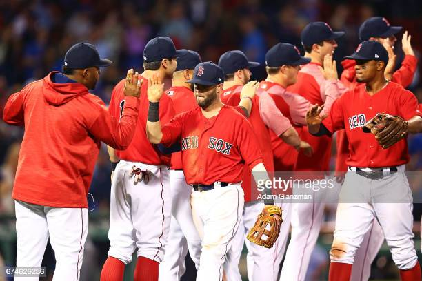 The Boston Red Sox high five each other after their victory over the Chicago Cubs at Fenway Park on April 28 2017 in Boston Massachusetts