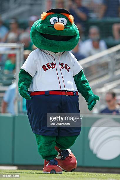 The Boston Red Sox mascot 'Wally the Green Monster' performs prior to the start of the spring training game against the Minnesota Twins at JetBlue...
