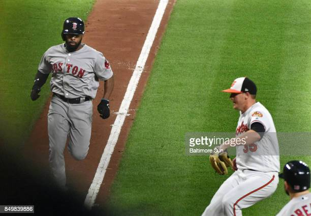 The Boston Red Sox's Jackie Bradley Jr left races for home ahead of Baltimore Orioles pitcher Brad Brach right who tries to cover home after throwing...