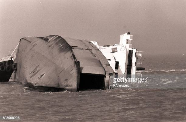 The bow end of the capsized car ferry Herald of Free Enterprise lies half submerged near the Belgian port of Zeebrugge, with the loading doors wide...