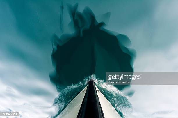 The bow of a boat passing over the still waters of an arctic fjord.