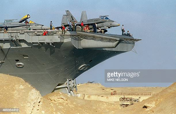 The bow of the aircraft carrier USS America looms above the sand dunes along the Suez Canal 15 January 1991 as an Egyptian army truck and...