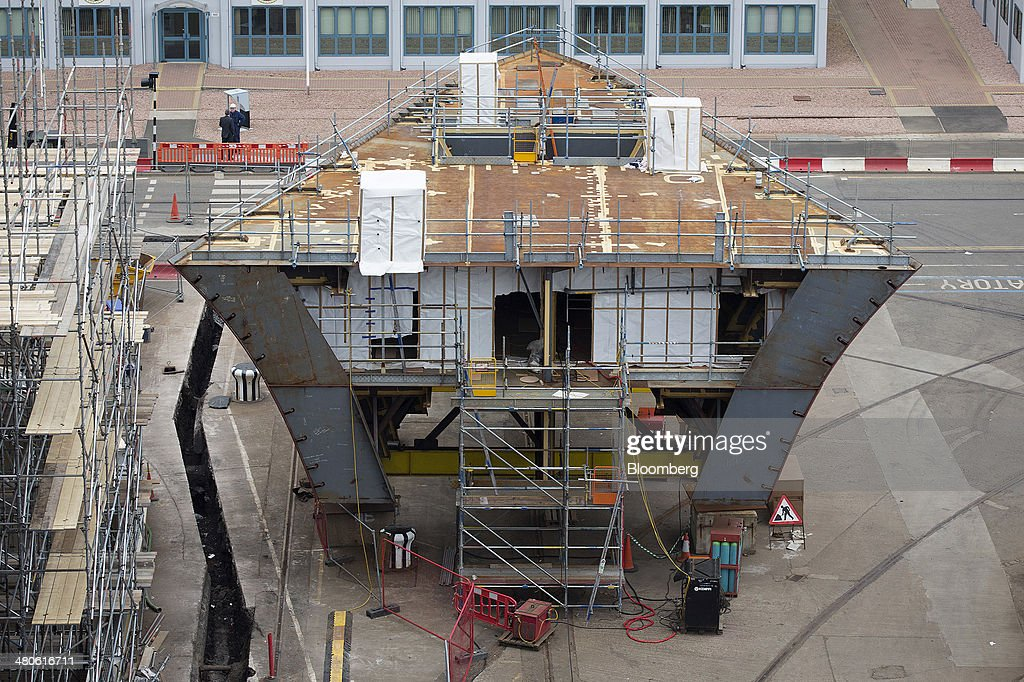 The bow section for the second of the Royal Navy's second Queen Elizabeth class aircraft carriers, The Prince of Wales, manufactured by the Aircraft Carrier Alliance, a joint operation between BAE Systems, Thales SA and Babcock International Group Plc, stands on the dock side at Babcock shipyard in Rosyth, U.K., on Tuesday, March 25, 2014. Construction of hull sections for the HMS Queen Elizabeth and HMS Prince of Wales aircraft carriers is being undertaken at BAE's Scotstoun and Govan yards on the River Clyde in Glasgow, with the ships due to be assembled at Babcock International Group's dockyard in Rosyth, near Edinburgh. Photographer: Simon Dawson/Bloomberg via Getty Images