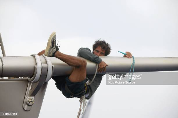 The bowman of the Wally yacht Dangerous but Fun hangs from the bowsprit following tripping the spinnaker from the end during racing in the Maxi Yacht...