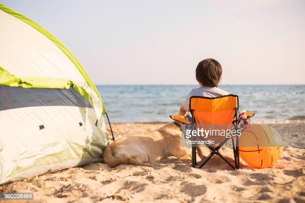 El muchacho y su perro es acampar en la playa