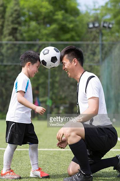 the boy and the coach face to face with football - head coach ストックフォトと画像