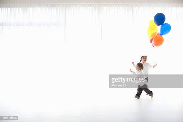 The boy and the girl are running with the balloon
