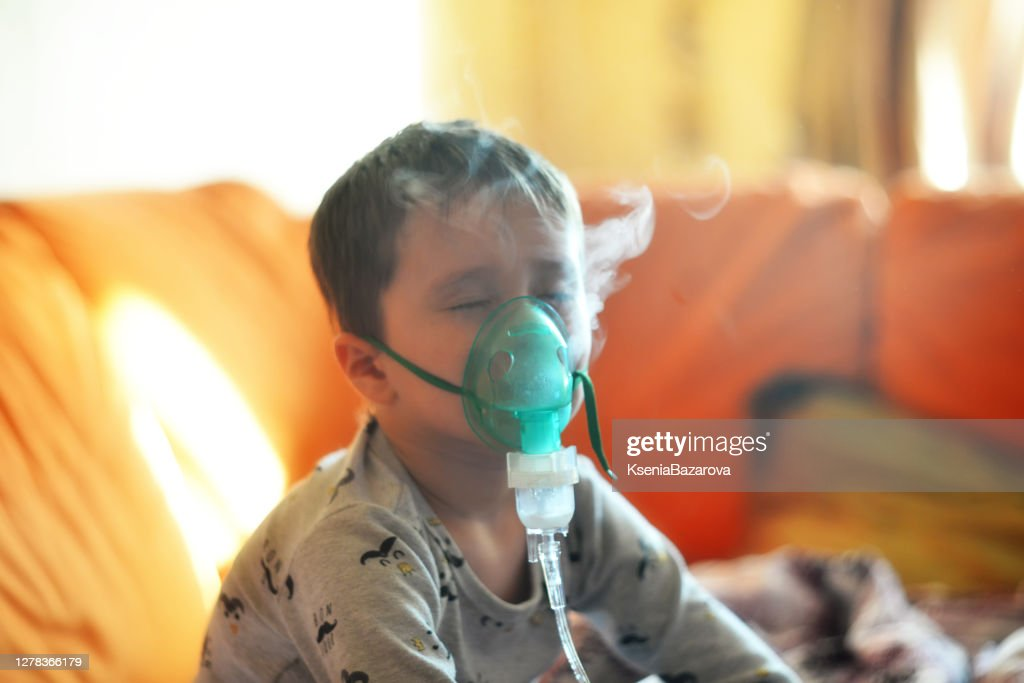 The boy breathes through the inhaler. The boy is being treated : Stock Photo