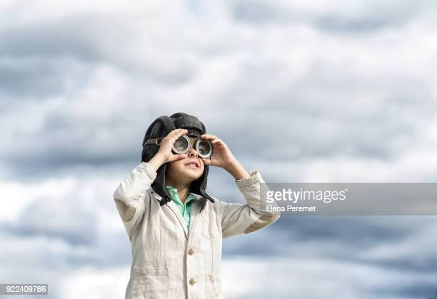 The boy in the Aviator helmet and glasses on the background of the sky