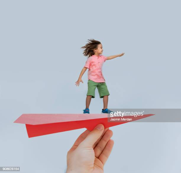 The boy is enjoying his flying on paper plane in father's hand