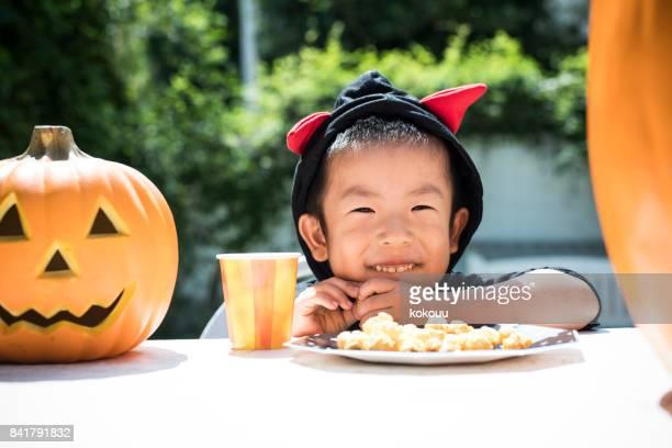 少年は、ハロウィーンの衣装を身に着けているポップコーンを食べるつもりです。