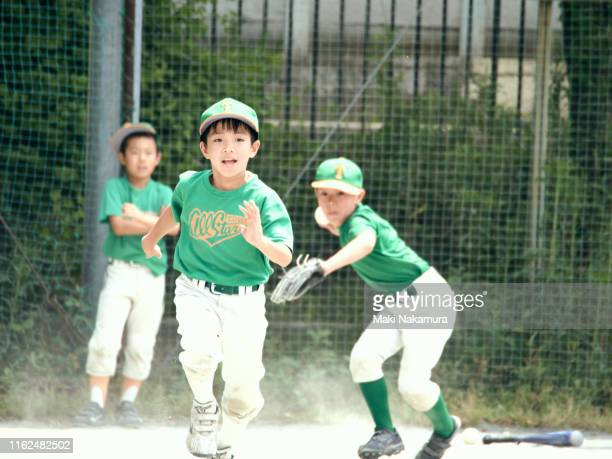 the boy is running at an enthusiastic speed toward the first base in a baseball game. - スポーツ  ストックフォトと画像