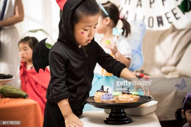 少年は、カップケーキをじっと見つめています。