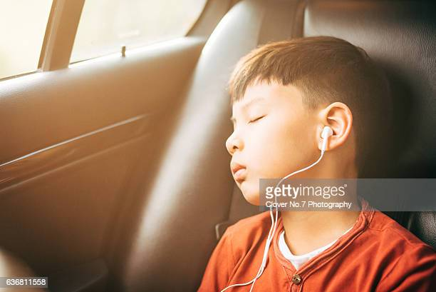 The boy listened to music with headphones.