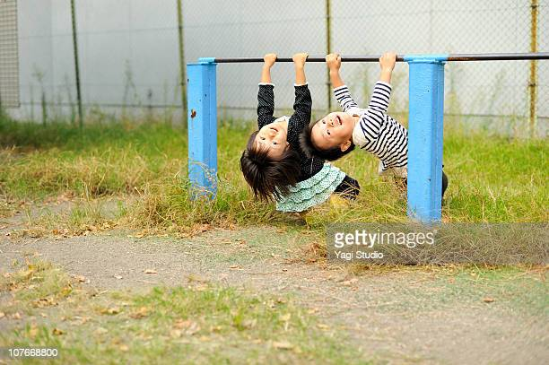 The boy playing a horizontal bar, and girl