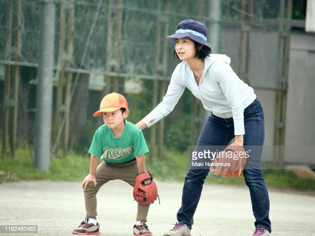 the boy protects the outfield with his mother in baseball practice - baseball mom stock pictures, royalty-free photos & images