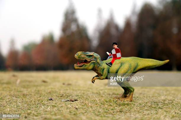 The boy riding on the back of the dinosaur, holding a shield and sword in his hand