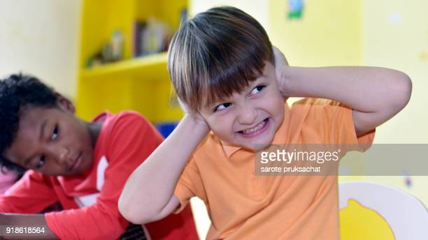 The boy used his hands to close his ears because he did not want to study  in an international school .Kindergarten, preschool, kids .