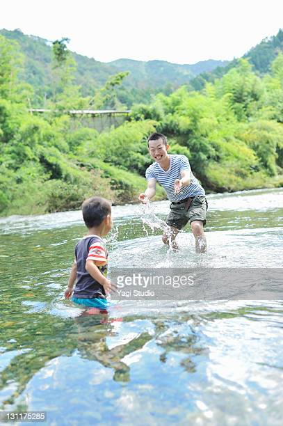 The boy who does dabbling in the river, and a youn