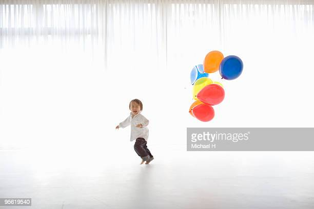 The boy who has the balloon is running