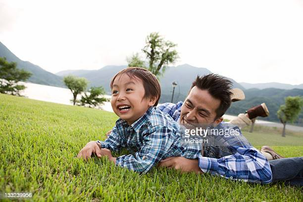 The boy who plays happily with a father on a lawn