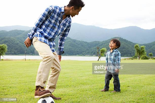 The boy who plays soccer happily with a father