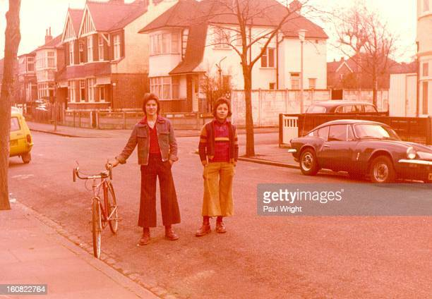 The boys are wearing typical 1970s clothes. The boy on the right is wearing a tank-top and his baggy trousers have been taken-up to show off his Dr...