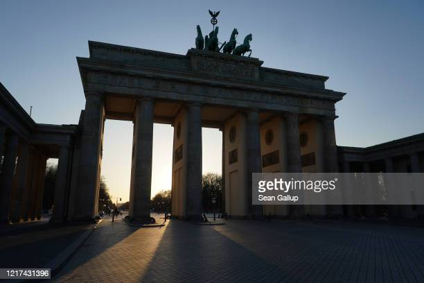The Brandenburg Gate, one of the city's main landmarks and a popular tourist destination, stands nearly devoid of visitors during the coronavirus...