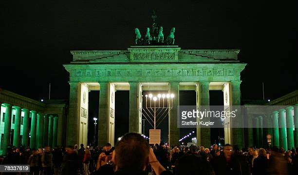 The Brandenburg Gate stands illuminated in green after the lights were switched off for five minutes during a nation-wide event to raise climate...