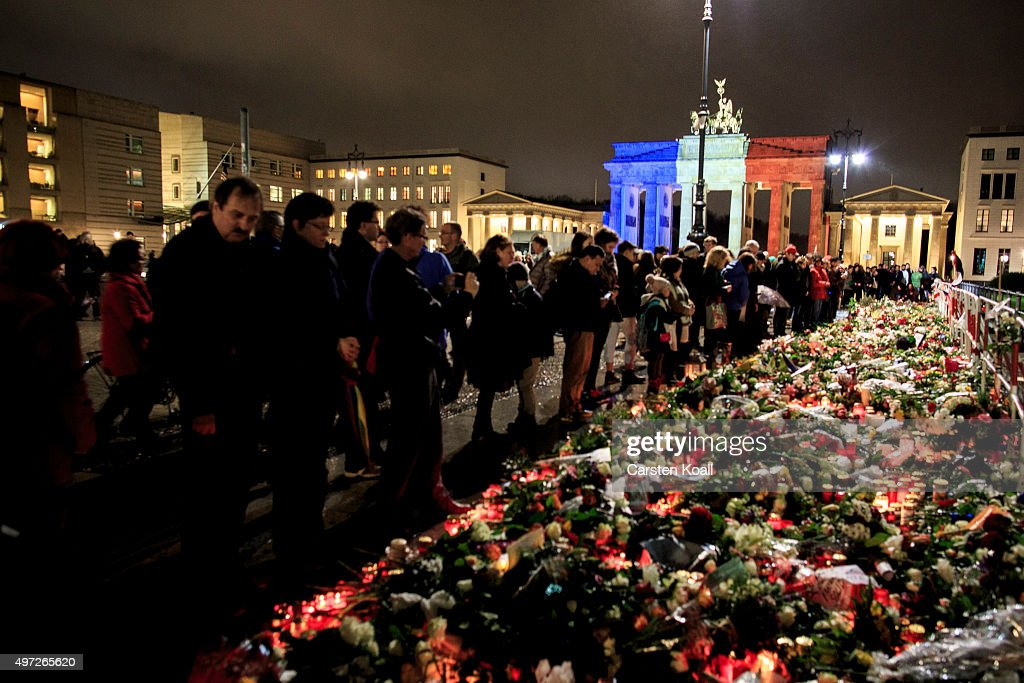 The Brandenburg Gate stands illuminated in the colors of the French flag as people lay candles and flowers at the gate of the nearby the French Embassy following the recent terror attacks in Paris on November 15, 2015 in Berlin, Germany. Hundreds of people came throughout the day to lay flowers, candles and messages of condolence to mourn the victims of attacks last friday night in Paris that left at least 160 people dead across the French capital. The Islamic State (IS) has claimed responsibility for the attacks that were carried out by at least eight terrorists.