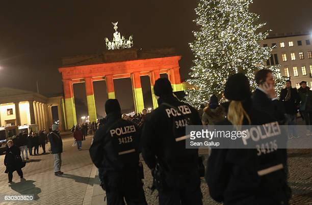 The Brandenburg Gate stands illuminated in the colors of the German flag as police walk past the day after a truck drove into a crowded Christmas...