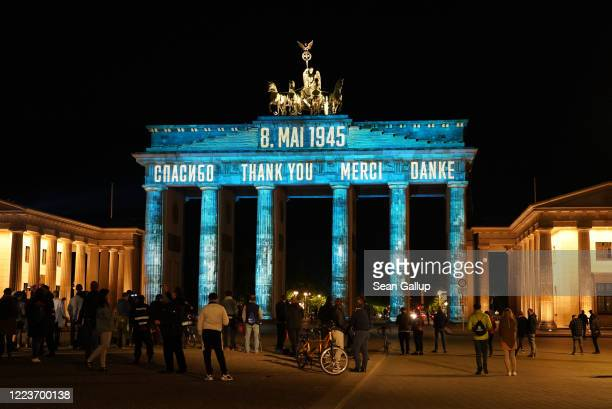 """The Brandenburg Gate stands illuminated with the word """"thank you"""" written in Russian, English, French and German as a message to the Allies who..."""